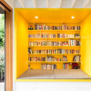 Immagine di un soggiorno design con libreria e pareti gialle