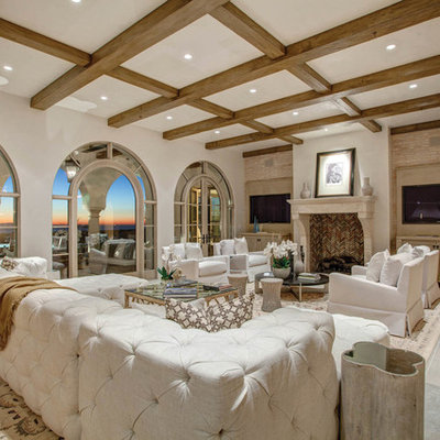Family room - mediterranean family room idea in Los Angeles with white walls, a standard fireplace and a wall-mounted tv