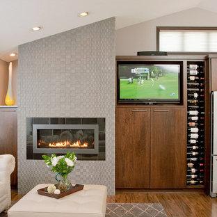 ミネアポリスの中サイズのコンテンポラリースタイルのおしゃれなファミリールーム (ベージュの壁、無垢フローリング、横長型暖炉、据え置き型テレビ、タイルの暖炉まわり、茶色い床) の写真
