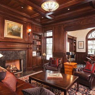 Diseño de sala de estar con biblioteca tradicional, sin televisor, con paredes marrones, suelo de madera oscura, chimenea tradicional y marco de chimenea de piedra