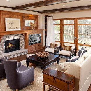 Modelo de sala de estar clásica con paredes beige, suelo de madera oscura, chimenea tradicional, marco de chimenea de piedra y pared multimedia