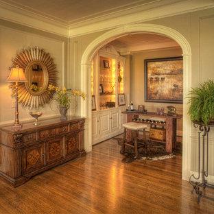 他の地域の巨大なトラディショナルスタイルのおしゃれなファミリールーム (ベージュの壁、無垢フローリング、暖炉なし、テレビなし、茶色い床) の写真