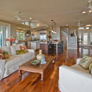Aménagement d'une salle de séjour exotique ouverte avec un mur beige, un sol en bois brun et un sol marron.