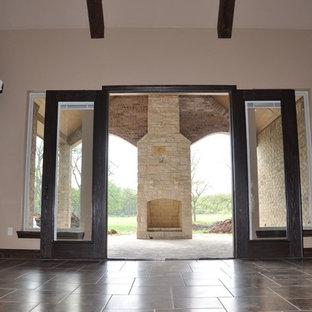 Ispirazione per un grande soggiorno stile rurale con pareti beige, camino classico, cornice del camino in mattoni, TV a parete e pavimento in travertino