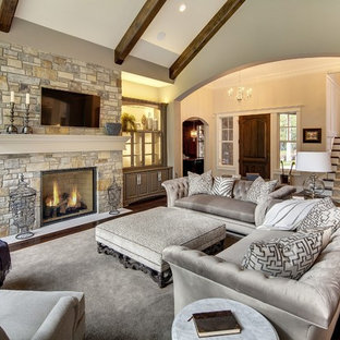 Large elegant enclosed dark wood floor and brown floor family room photo in Minneapolis with beige walls, a standard fireplace, a stone fireplace and a wall-mounted tv