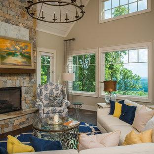 Idée de décoration pour une salle de séjour craftsman de taille moyenne avec un mur beige, un sol en bois foncé, une cheminée standard, un manteau de cheminée en pierre et un téléviseur dissimulé.