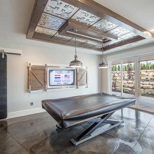 Idee per un grande soggiorno industriale aperto con sala giochi, pareti grigie, pavimento in cemento, nessun camino e TV nascosta