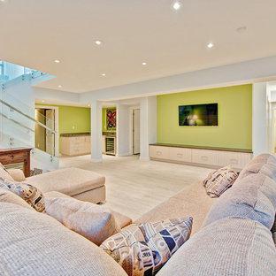 Immagine di un grande soggiorno design chiuso con pareti blu, pavimento in laminato e TV a parete