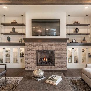 コロンバスの中サイズのトラディショナルスタイルのおしゃれなファミリールーム (ベージュの壁、無垢フローリング、標準型暖炉、レンガの暖炉まわり、壁掛け型テレビ、茶色い床) の写真