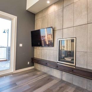 カルガリーの巨大なインダストリアルスタイルのおしゃれなファミリールーム (ホームバー、グレーの壁、無垢フローリング、標準型暖炉、タイルの暖炉まわり、壁掛け型テレビ) の写真