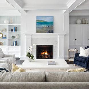 ミネアポリスのビーチスタイルのおしゃれなファミリールーム (白い壁、濃色無垢フローリング、標準型暖炉、石材の暖炉まわり、茶色い床) の写真