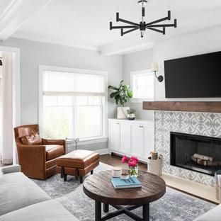Ejemplo de sala de estar abierta, campestre, con paredes grises, suelo de madera en tonos medios, chimenea tradicional, marco de chimenea de baldosas y/o azulejos, televisor colgado en la pared y suelo marrón