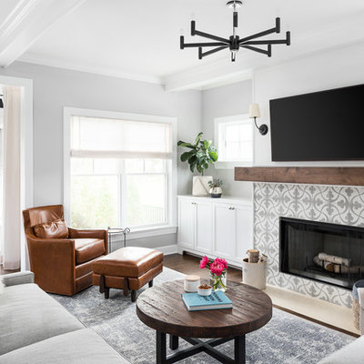 Example of a farmhouse open concept medium tone wood floor and brown floor family room design in Chicago with gray walls, a standard fireplace, a tile fireplace and a wall-mounted tv