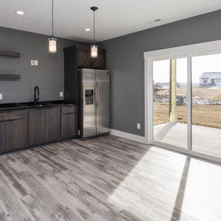 Foto di un grande soggiorno minimalista aperto con pareti grigie, pavimento grigio, angolo bar, pavimento in vinile, nessun camino e TV a parete