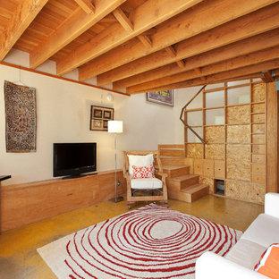 サンフランシスコのコンテンポラリースタイルのおしゃれなファミリールーム (ベージュの壁、コンクリートの床、据え置き型テレビ) の写真