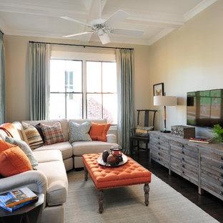 Modelo de sala de estar cerrada, clásica renovada, pequeña, con paredes beige, suelo de madera en tonos medios y televisor colgado en la pared