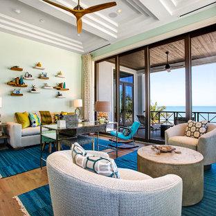 Cette photo montre une salle de séjour exotique avec un mur vert et un sol en bois brun.