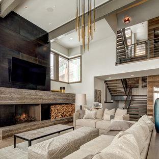 Imagen de sala de estar abierta, actual, grande, con paredes beige, chimenea tradicional, televisor colgado en la pared, suelo de madera oscura, marco de chimenea de hormigón y suelo marrón