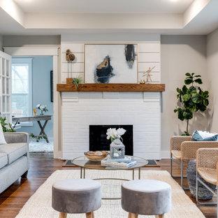 Idées déco pour une grand salle de séjour craftsman ouverte avec un mur gris, un sol en bois brun, une cheminée standard, un manteau de cheminée en brique et un sol marron.