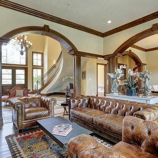 ヒューストンの大きい地中海スタイルのおしゃれなファミリールーム (ベージュの壁、暖炉なし、テレビなし、茶色い床、無垢フローリング) の写真