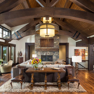 Cette photo montre une grande salle de séjour montagne ouverte avec un mur blanc, un sol en bois brun, une cheminée standard, un manteau de cheminée en pierre, un sol marron et un téléviseur dissimulé.