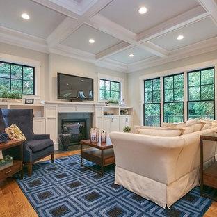 Foto de sala de estar abierta, campestre, grande, con paredes grises, suelo de madera en tonos medios, chimenea tradicional, marco de chimenea de piedra, televisor colgado en la pared y suelo marrón