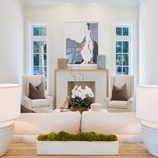 Inspiration pour une salle de séjour mansardée ou avec mezzanine ethnique de taille moyenne avec un mur blanc, un sol en bois clair, une cheminée standard, un manteau de cheminée en plâtre, aucun téléviseur et un sol beige.