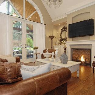 バンクーバーのトラディショナルスタイルのおしゃれなファミリールーム (ベージュの壁、無垢フローリング、標準型暖炉、壁掛け型テレビ) の写真