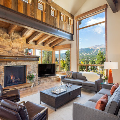 Inspiration for a rustic open concept medium tone wood floor family room remodel in Denver with beige walls, a standard fireplace, a stone fireplace and a corner tv