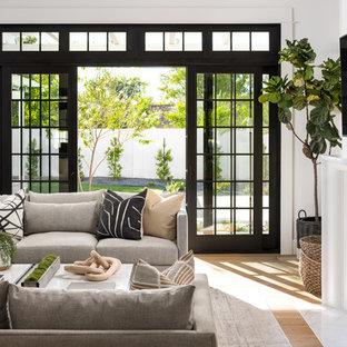 Diseño de sala de estar abierta, de estilo de casa de campo, grande, con paredes blancas, suelo de madera clara, chimenea tradicional, marco de chimenea de piedra y televisor colgado en la pared