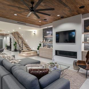 オレンジカウンティのコンテンポラリースタイルのおしゃれなファミリールーム (白い壁、横長型暖炉、金属の暖炉まわり、壁掛け型テレビ、ベージュの床) の写真