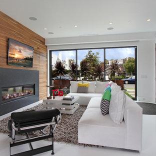 Idée de décoration pour une salle de séjour design avec un mur blanc, une cheminée ribbon, un téléviseur fixé au mur et un sol blanc.