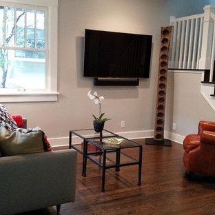 Modelo de sala de estar cerrada, clásica renovada, pequeña, con paredes grises, suelo de madera oscura y televisor colgado en la pared