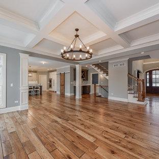 Idee per un grande soggiorno classico stile loft con pareti grigie, pavimento in laminato, camino sospeso, cornice del camino in pietra, nessuna TV e pavimento marrone