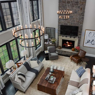 Example of a large trendy open concept dark wood floor family room design in Baltimore with gray walls, a standard fireplace, a stone fireplace and a wall-mounted tv