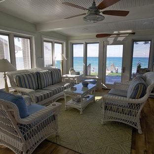 Idées déco pour une salle de séjour bord de mer de taille moyenne et ouverte avec un mur vert, un sol en bois brun et aucune cheminée.