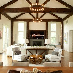 Diseño de sala de estar abierta, campestre, extra grande, con suelo de madera en tonos medios, chimenea tradicional, marco de chimenea de piedra y televisor colgado en la pared
