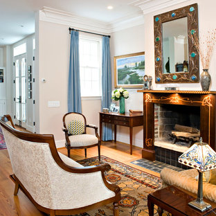 Example of a classic medium tone wood floor family room design in DC Metro with beige walls and a standard fireplace