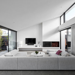 This is an example of a large contemporary open concept family room in Melbourne with white walls, concrete floors, a wall-mounted tv, grey floor and a wood stove.