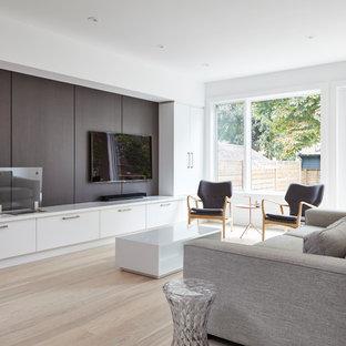 Inspiration pour une salle de séjour mansardée ou avec mezzanine minimaliste de taille moyenne avec un mur blanc, un sol en bois clair, une cheminée ribbon, un manteau de cheminée en bois, un téléviseur encastré et un sol multicolore.