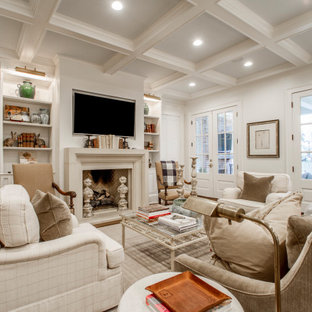 Inspiration for a large timeless open concept medium tone wood floor and brown floor family room remodel in Little Rock with white walls, a standard fireplace, a plaster fireplace and a wall-mounted tv