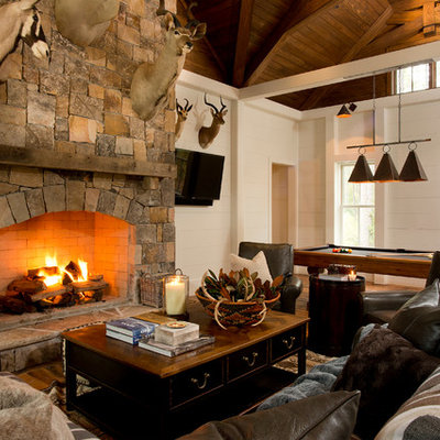 Inspiration for a rustic medium tone wood floor family room remodel in Atlanta with white walls, a standard fireplace, a stone fireplace and a wall-mounted tv