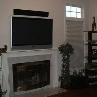 Immagine di un soggiorno chic di medie dimensioni e aperto con pareti bianche, camino classico, cornice del camino in pietra, TV a parete e parquet scuro