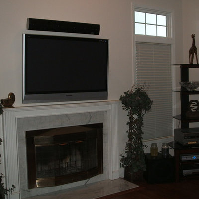 Inspiration for a mid-sized timeless open concept dark wood floor family room remodel in New York with white walls, a standard fireplace, a stone fireplace and a wall-mounted tv