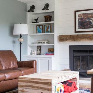 オタワの中サイズのラスティックスタイルのおしゃれな独立型ファミリールーム (青い壁、淡色無垢フローリング、標準型暖炉、木材の暖炉まわり、据え置き型テレビ) の写真