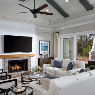 Idee per un soggiorno stile marino con TV a parete, pareti grigie, pavimento in legno massello medio, camino lineare Ribbon e cornice del camino in mattoni