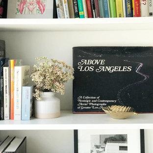ロサンゼルスの中サイズのコンテンポラリースタイルのおしゃれなファミリールーム (ゲームルーム、白い壁、コンクリートの床、暖炉なし、コンクリートの暖炉まわり、壁掛け型テレビ、グレーの床) の写真