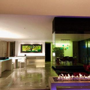 Esempio di un ampio soggiorno chic stile loft con pareti beige, pavimento in pietra calcarea, camino bifacciale, cornice del camino in cemento, nessuna TV e pavimento grigio