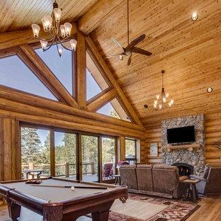 デンバーの広いラスティックスタイルのおしゃれなオープンリビング (ゲームルーム、ベージュの壁、無垢フローリング、標準型暖炉、石材の暖炉まわり、茶色い床) の写真