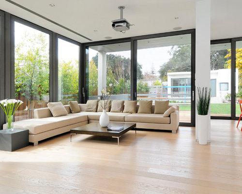 trendy open concept light wood floor and beige floor family room photo in san francisco